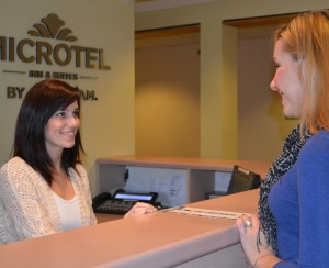 A customer is greeted at the front desk of the Victor Microtel Inn & Suites by Wyndham by Sally Clarke, operations manager ​and Indus team member.